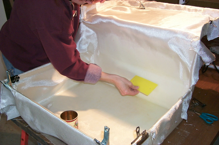 Laying in fiberglass and resin to shower pan.
